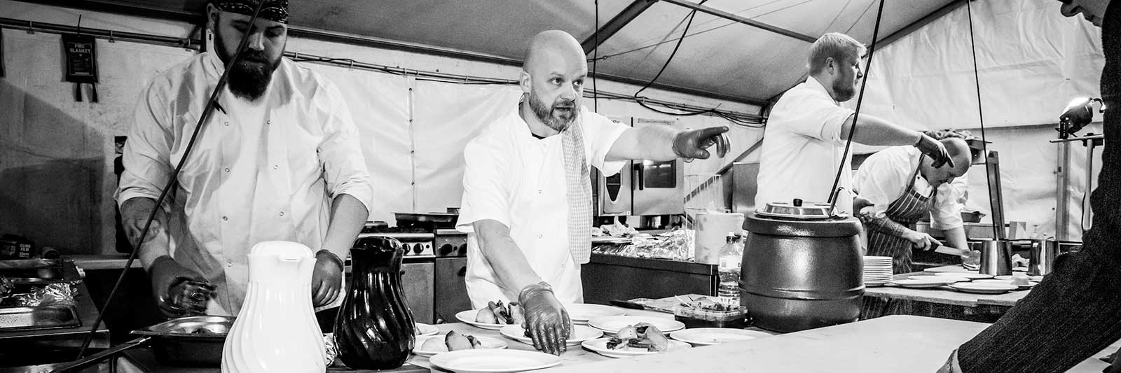 Black and white photo of four chefs working in a marquee kitchen